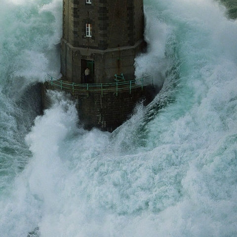 Water rushing by a lighthouse